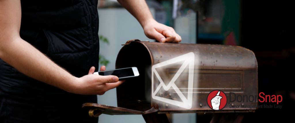 Image of person holding phone up to mail box with email graphic